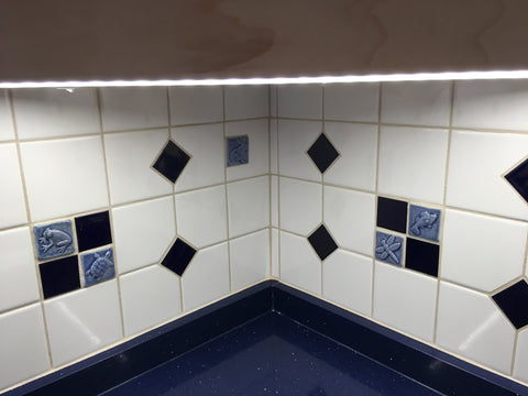 blue handmade animal tiles installed in a kitchen