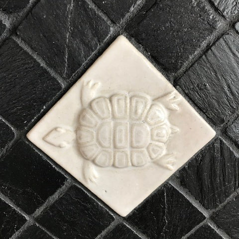black and white back splash featuring handmade tiles and slate, turtle tile close up