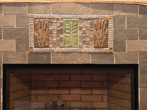 close up of handmade tiles installed over a fireplace insert