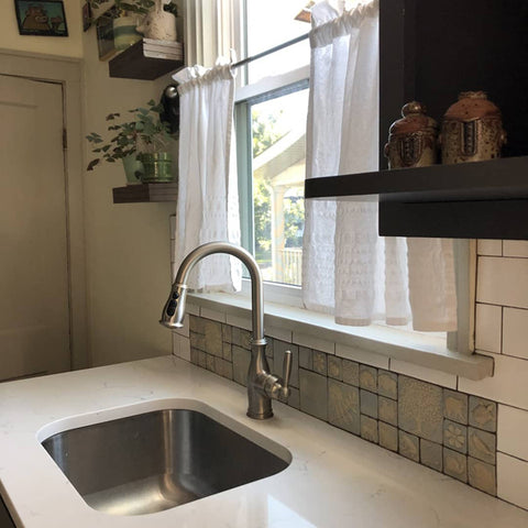 periwinkle handmade tiles featuring plants and animals installed in a kitchen sink backsplash