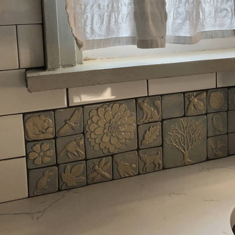 close up of handmade tiles in a light purple glaze featuring plants and animals, installed with with subway tiles in a newly remolded  kitchen