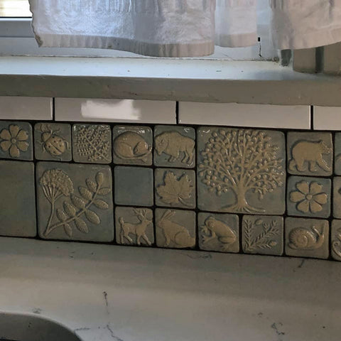 close up of handmade tiles featuring plants and animals installed in a kitchen backslash