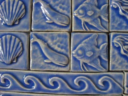close up of blue art tiles depicitng sea creatures and waves