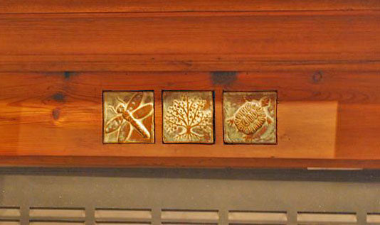 art tiles in a wooden fireplace surrpuound- dragonflu, tree, turtle