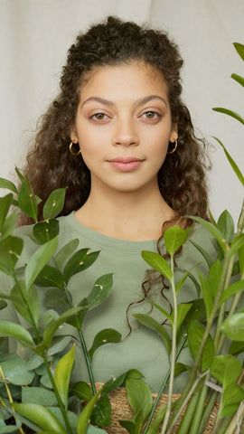 plant based skincare woman standing by plant