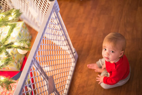 baby sitting in front of christmas tree with baby gate