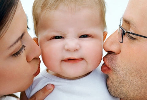 parents kissing infant