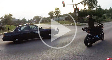 COP SWERVES AT MOTORCYCLE STUNT RIDERS