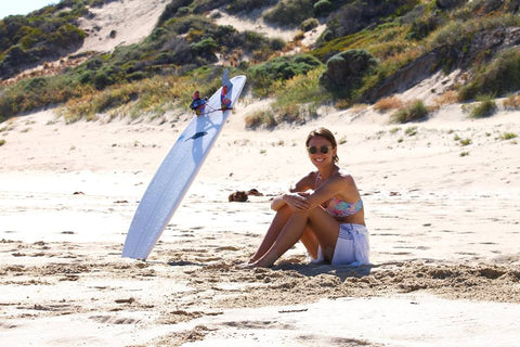 Founder of LAYA bikini with surfboard
