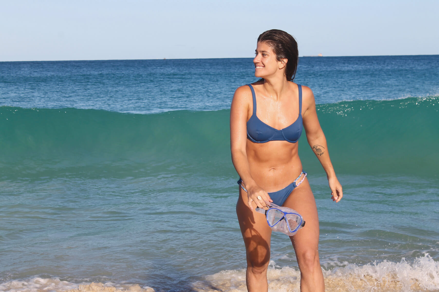 woman in blue bikini at beach holding goggles