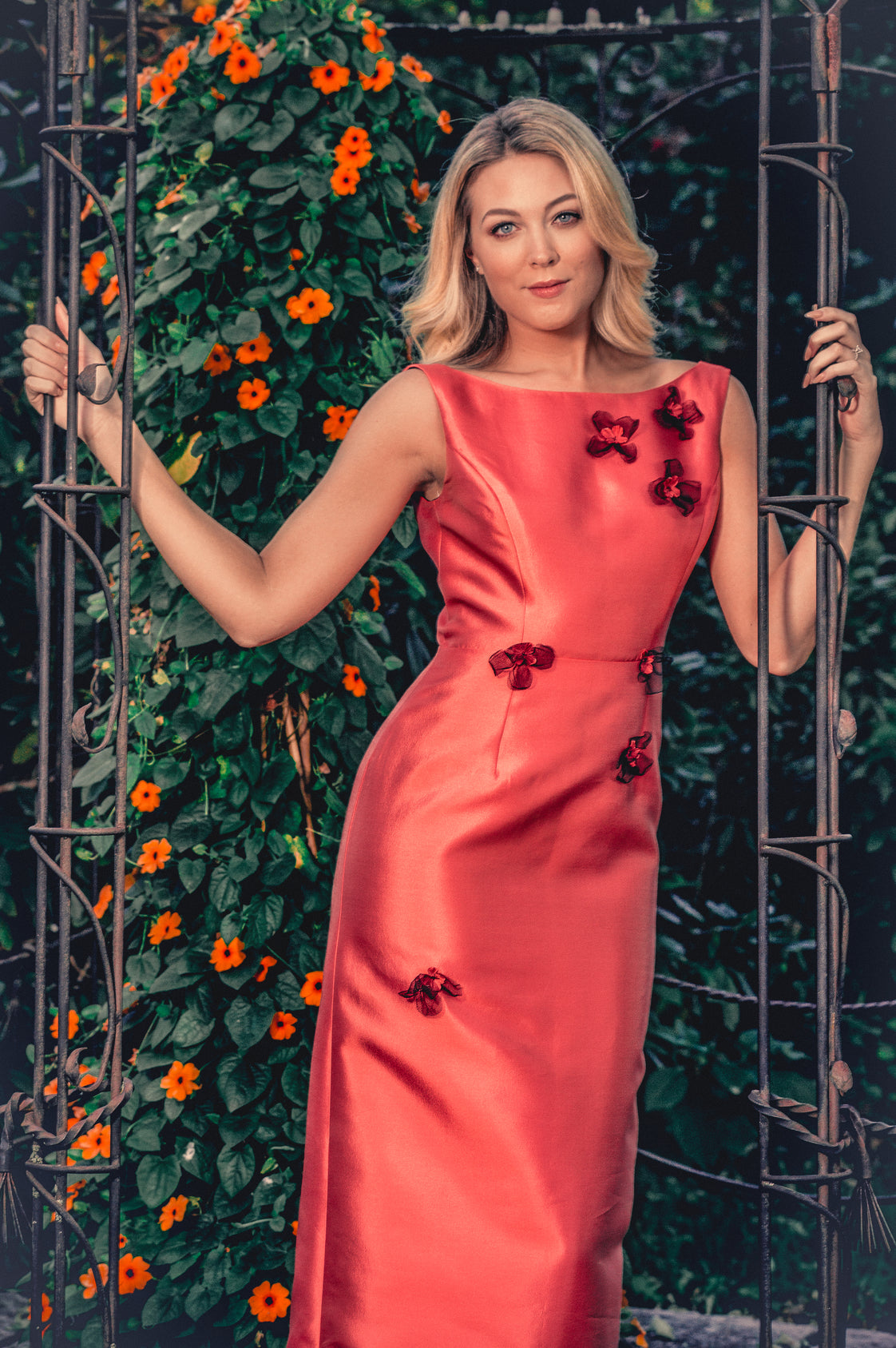 anna nieman designer dress Boston. A dress in vibrant salmon, with a column silhouette and appliquéd with delicate and dramatic black flowers. A favorite of many!