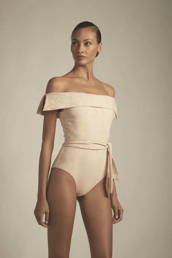 A birch colored one-piece swimsuit that features a sash-like belted waist, and an off-the-shoulder design. Comprised of luxurious toile fabric this maillot is absolutely divine and one-of-a-kind.