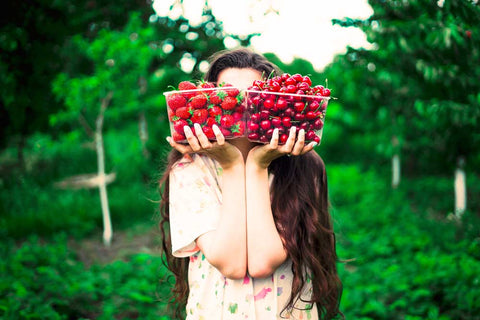 Girl with cherries and strawberries