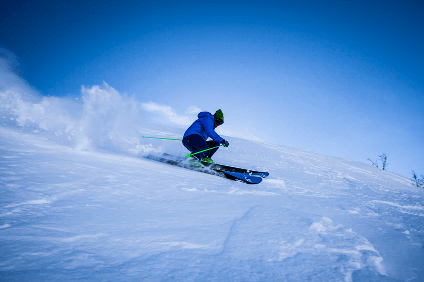 Man snow skiing down a slope wearing blue jacket