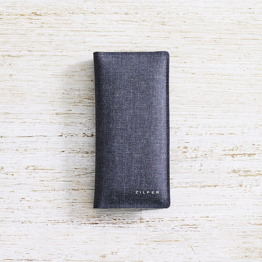 Zilfer Phone Wallet In Grey Closed On Light Wood Desk