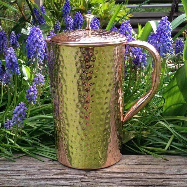 Shantiva copper pitcher placed on a wooden bench with blue flowers as background