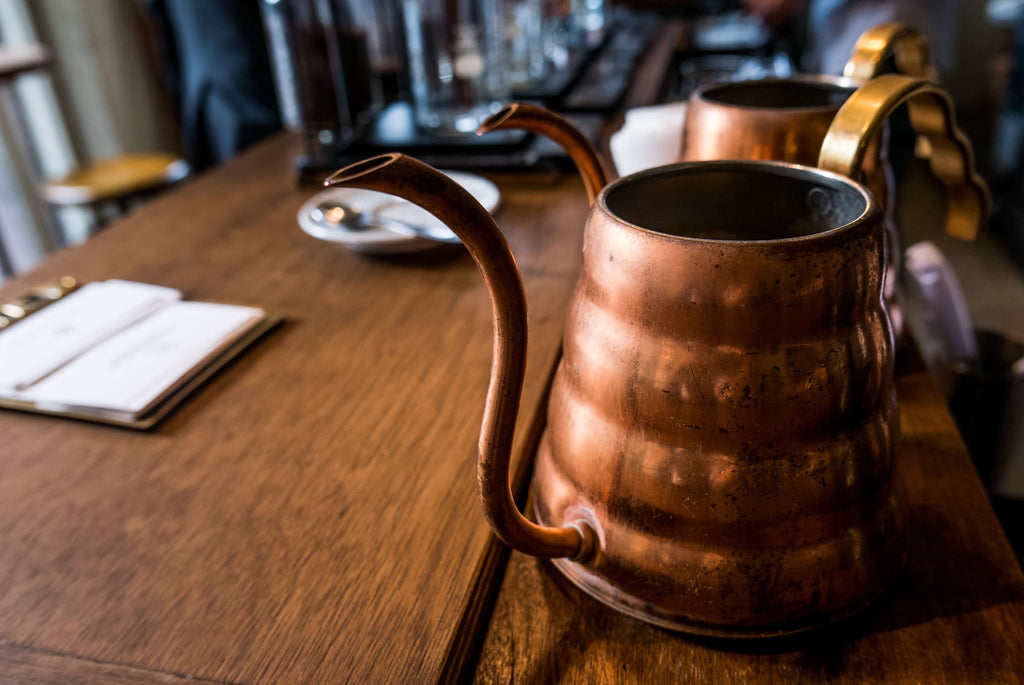 vintage copper pitchers placed on a long wooden dinning table