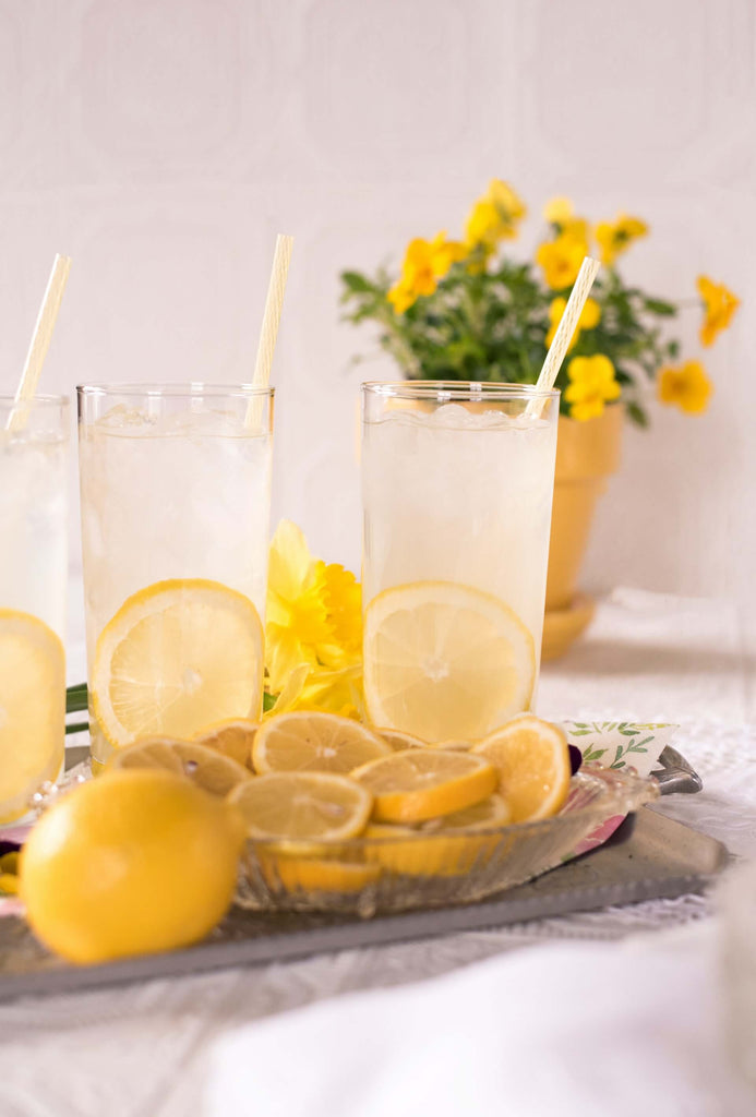 3 clear glasses filled with water and piece of sliced lemon and a straw in each