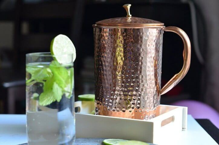 Shantiva copper pitcher placed on a wooden table beside a glass filled with water