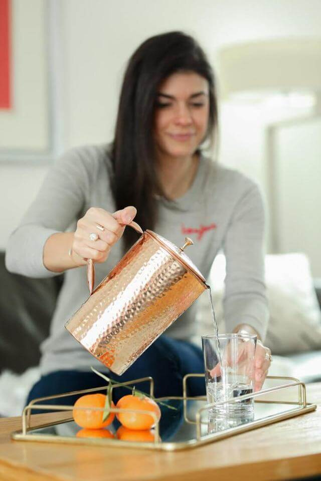 woman pouring water from a Shantiva copper pitcher into a glass