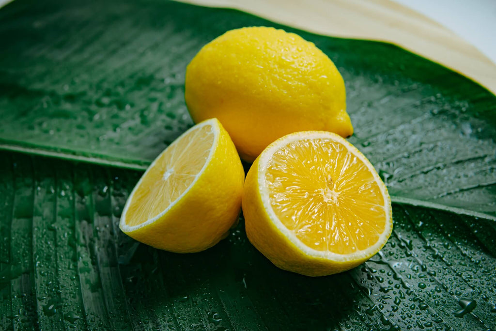 one lemon sliced in half and one whole lemon placed on a green leaf