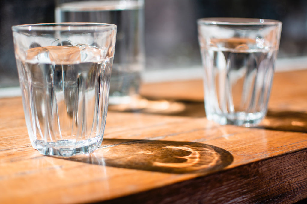 three clear drinking glass with water inside placed on top of a wooden table