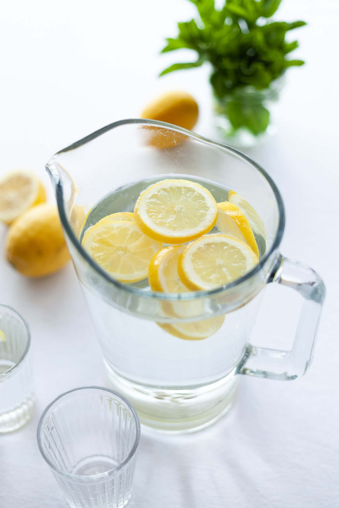 clear pitcher filled with water and pieces of sliced lemon