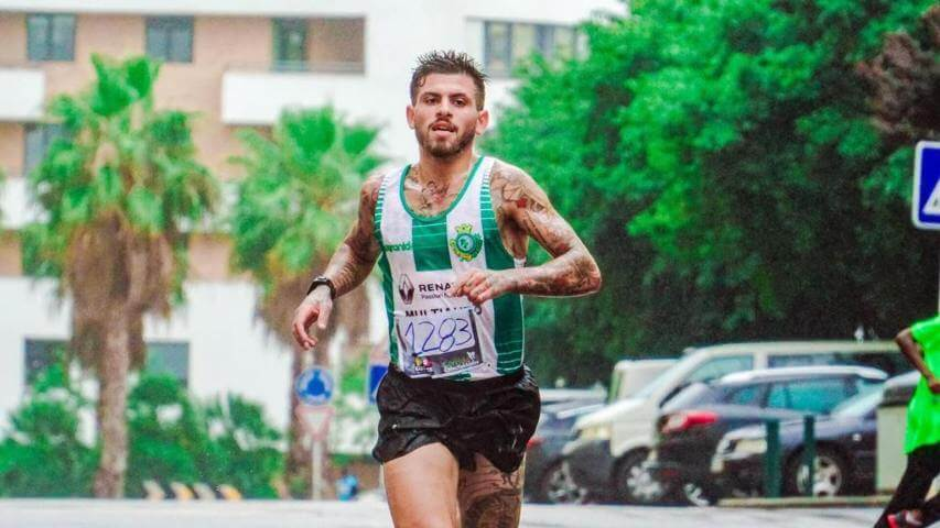 man with tatoos running a race wearing sports attire
