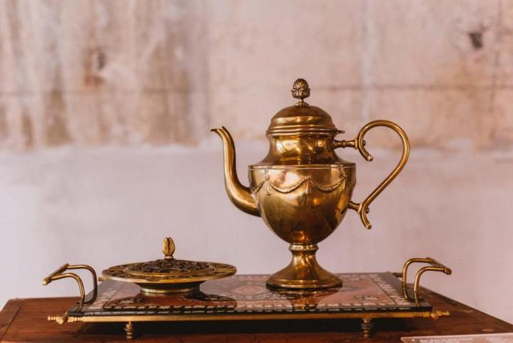 elaborate gold teapot placed on a tray
