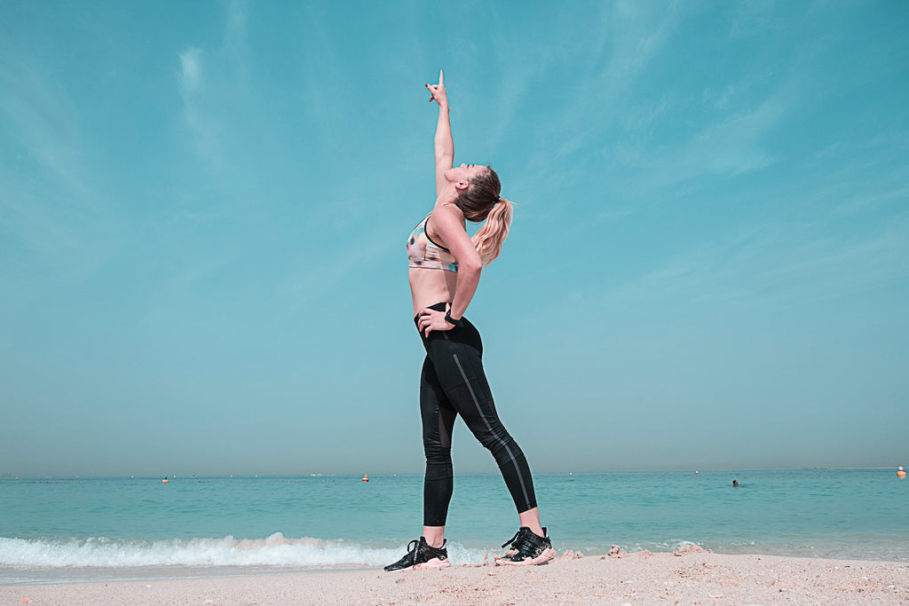 woman in athletic wear pointing upward standing on the beach shore