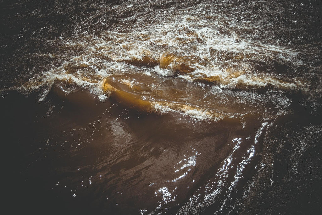 brown body of water waved forming a whirlpool