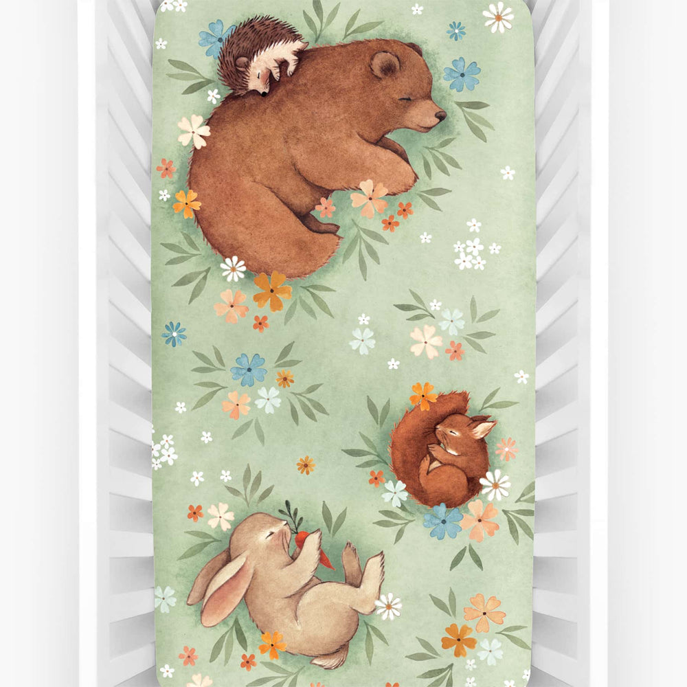 Rookie Humans crib sheet Enchanted Meadow. Floral crib sheet with sleeping bear, squirrel, hedgehog and bunny. Light green crib sheet, woodland theme, floral theme.