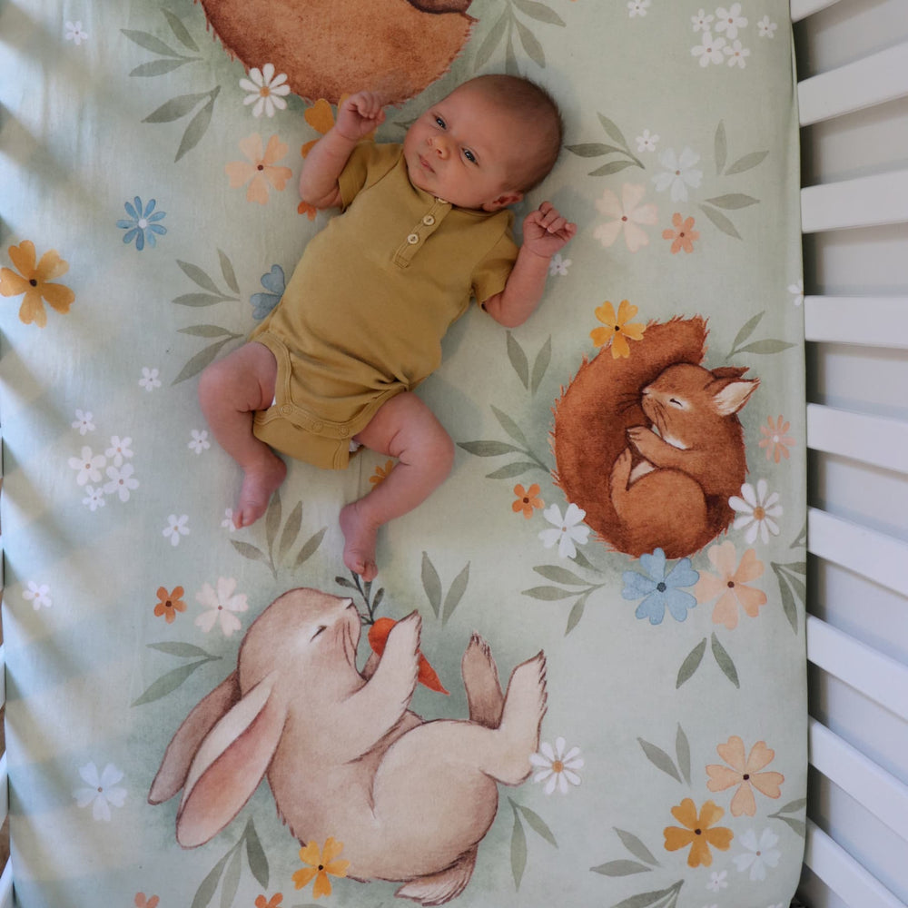 Rookie Humans crib sheet Enchanted Meadow. Floral crib sheet with sleeping bear, squirrel, hedgehog and bunny. Light green crib sheet, woodland theme, floral theme. Boho nursery, floral nursery, boho crib sheet, boho baby.