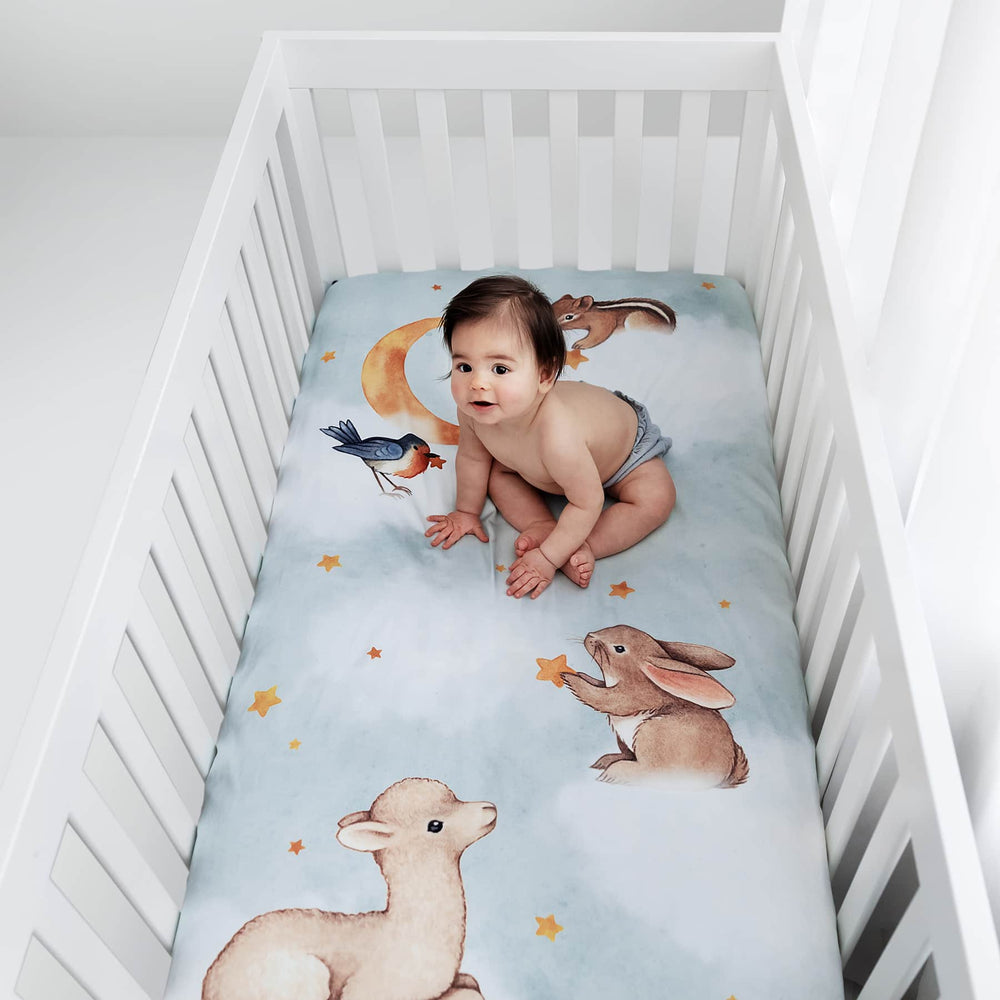 Rookie Humans crib sheet Goodnight Wonderland, fitted crib sheet with llama bunny bird moon stars and chipmunk. Light blue crib sheet with clouds.