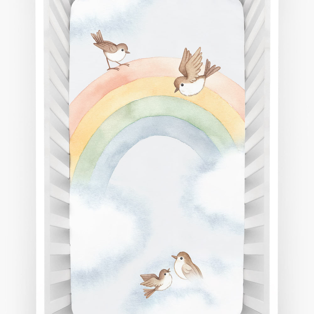 Baby crib sheet with watercolor rainbow design, light blue background, birds and clouds