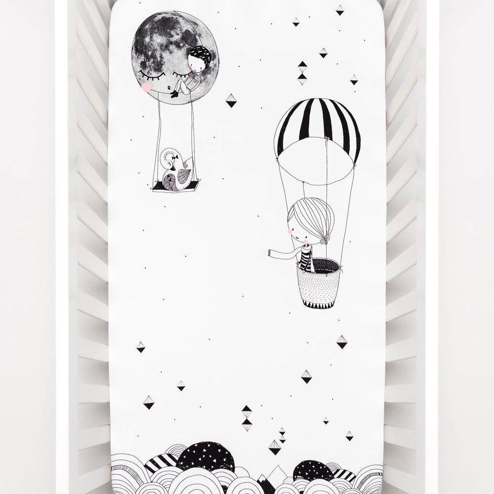 Fitted baby crib sheet by Rookie Humans, Frieda and the hot air balloon. Illustrated by Swanjte Hinrichsen. Designed for the modern nursery, packaged to make a unique baby shower gift. Monochrome nursery.