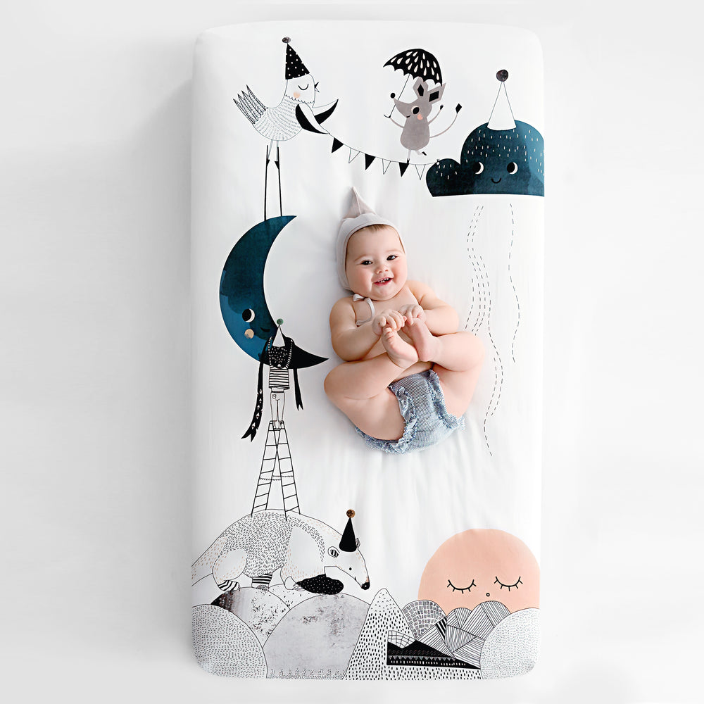 Fitted baby crib sheet by Rookie Humans, The Moon's Birthday. Illustrated by Swanjte Hinrichsen. Designed for the modern nursery, packages to make a unique baby shower gift.
