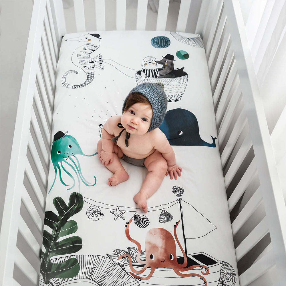 Fitted baby crib sheet by Rookie Humans, Underwater Love. Illustrated by Swanjte Hinrichsen. Designed for the modern nursery, packaged to make a unique baby shower gift. Nautical and ocean theme.