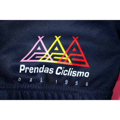 Macro photograph detailing the three different coloured Prendas logos on the jersey.