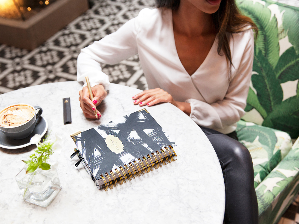 Woman sitting at table with coffee and a diary, writing.