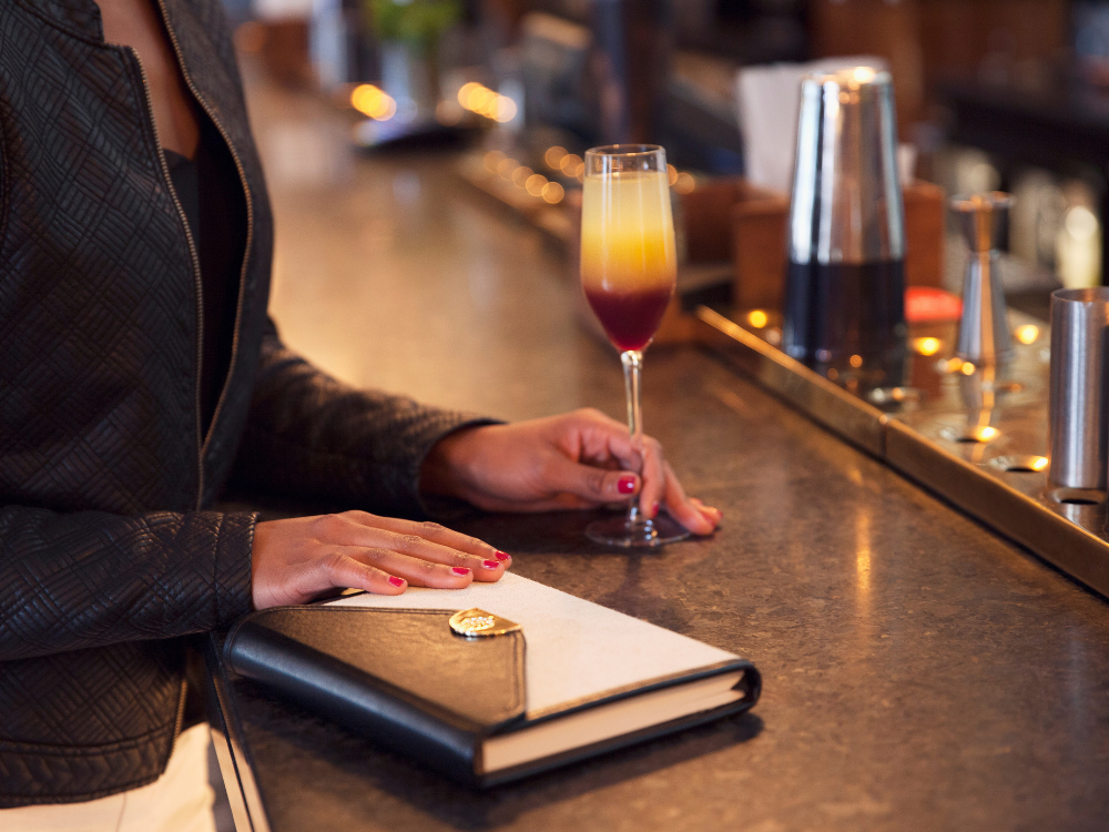 woman stood at a bar with a notebook and cocktail