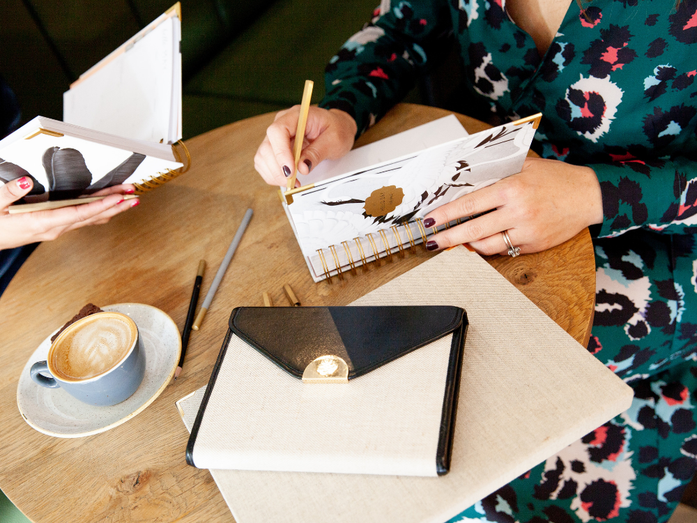 woman sat at table writing in a planner