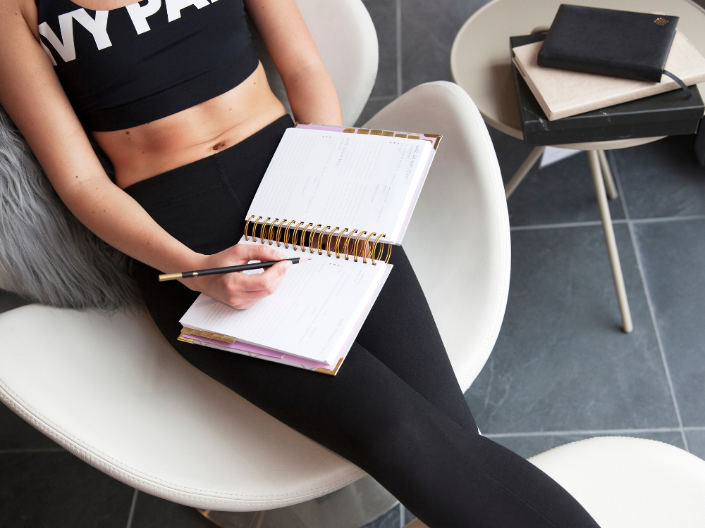 woman in gym kit relaxing with a day planner diary