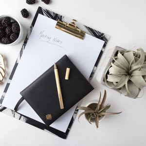 Brass Pen on Journal and Clipboard