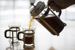 A back lit image of coffee being poured into small coffee mugs from a French Press with the light source being a window behind the table.