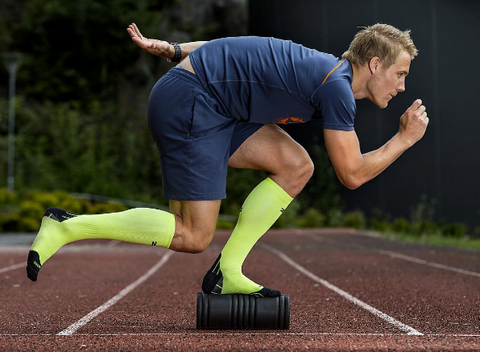 Athlete balancing on a foam roller with Zensah Compression Socks in Neon Green