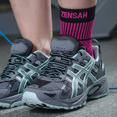 zoom in picture of a woman wearing the Zensah pink ankle support sleeve