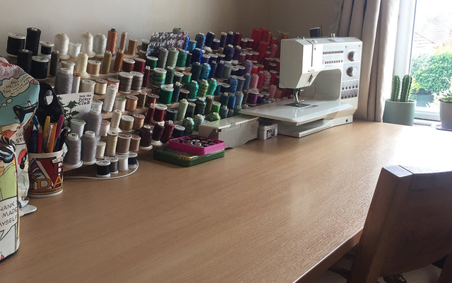 A tidy sewing space with lots of threads and a sewing machine on the table