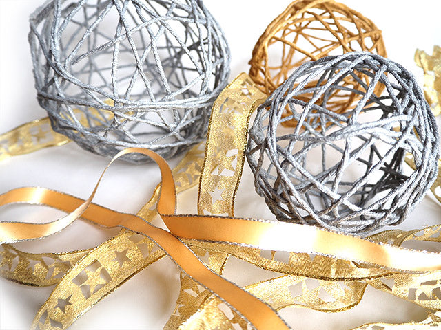 Handmade silver and gold string decorations with ribbons