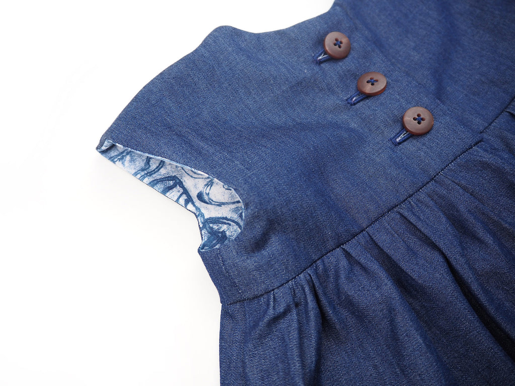 Button detail on a handmade denim girl's dress